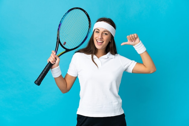 Young hispanic woman over isolated blue playing tennis and proud of himself