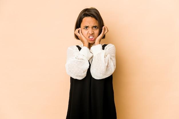 젊은 히스패닉 여자는 손가락으로 귀를 덮고, 스트레스를 받고 시끄러운 분위기에 절망적입니다.