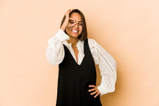 Молодая латиноамериканская женщина изолировала возбужденное, держа одобренный жест на глазах.