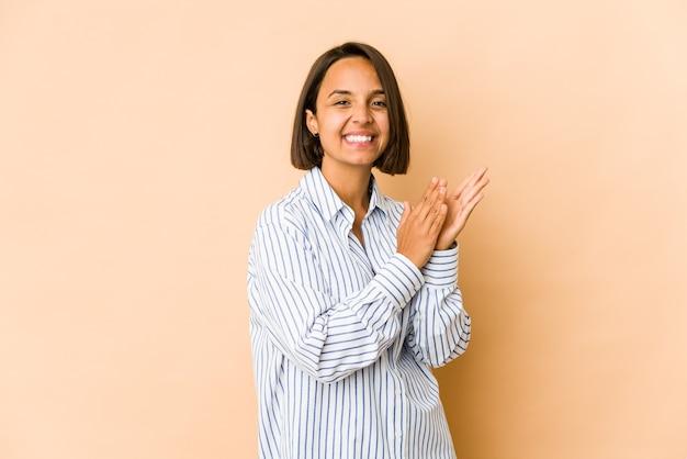 Молодая латиноамериканская женщина чувствует себя энергичной и комфортной, уверенно потирая руки.