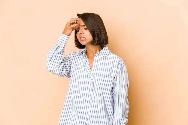 Молодая латиноамериканская женщина изолирована от головной боли, касаясь передней части лица.