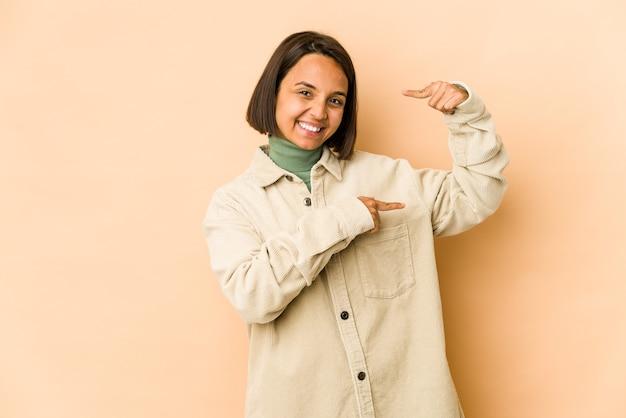 Молодая испаноязычная женщина изолировала, держа что-то немного указательными пальцами, улыбаясь и уверенно.