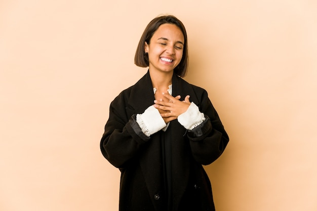 Young hispanic woman isolated laughing keeping hands on heart, concept of happiness.