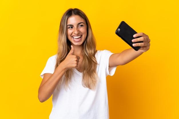 Молодая латиноамериканская женщина изолирована, делая селфи с мобильным телефоном