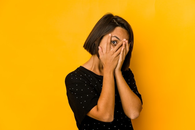 Молодая латиноамериканская женщина, изолированная на желтом мигании, испугалась и нервничала