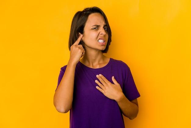 Молодая латиноамериканская женщина изолирована на желтом прикрытии ушей пальцами, подчеркнутая и отчаянная из-за громкого окружения.