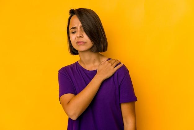 Молодая латиноамериканская женщина изолирована на желтом с болью в плече