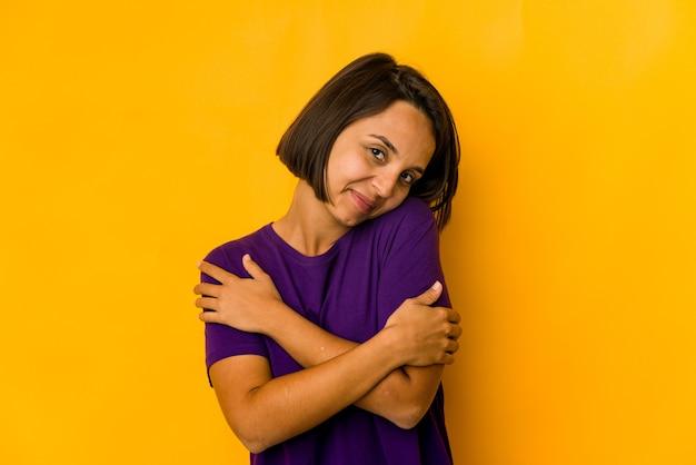 Молодая латиноамериканская женщина, изолированная на желтых объятиях, беззаботно улыбается и счастлива.