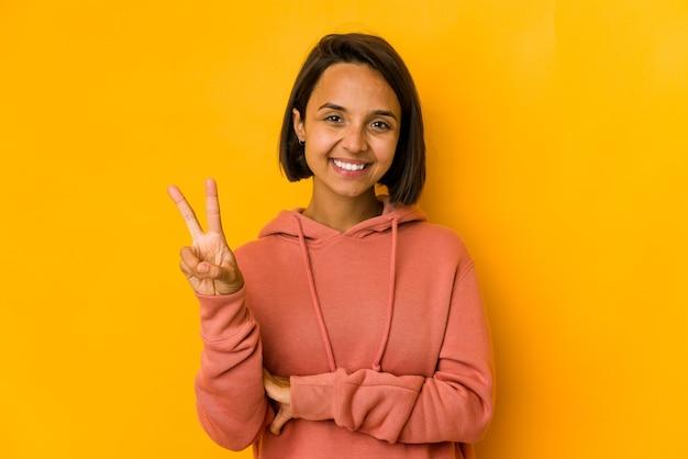 指で平和のシンボルを示す黄色のうれしそうなのんきで孤立した若いヒスパニック系の女性。