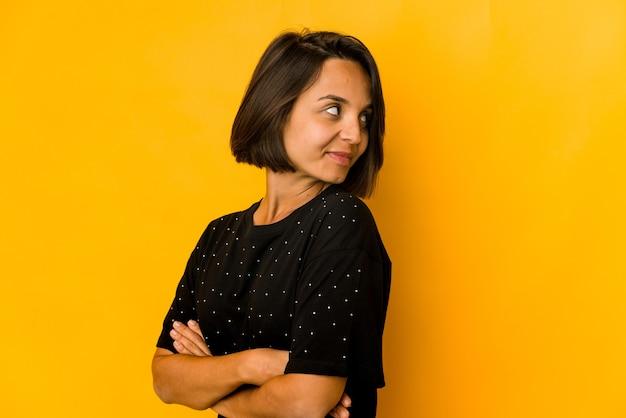 Молодая латиноамериканская женщина, изолированная на желтом, смотрит в сторону улыбающейся, веселой и приятной.