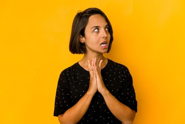 Молодая латиноамериканская женщина изолирована на желтом, составляя план в уме, создавая идею.