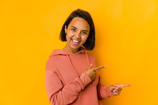Молодая латиноамериканская женщина изолирована на желтом, указывая указательными пальцами на место для копирования, выражая волнение и желание.