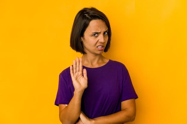 Молодая латиноамериканская женщина изолирована на желтом, отвергая кого-то, показывая жест отвращения.