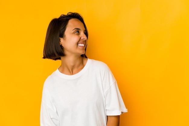Молодая латиноамериканская женщина изолирована на желтом расслабленном и счастливом смехе, вытянув шею, показывая зубы