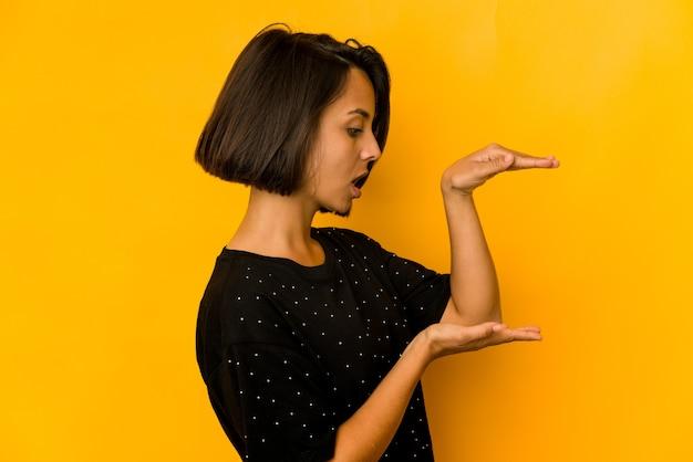 Молодая латиноамериканская женщина, изолированная на желтом, потрясена и поражена, держа между руками копию пространства.