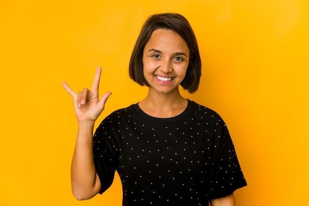 혁명 개념으로 뿔 제스처를 보여주는 노란색에 고립 된 젊은 히스패닉 여자.