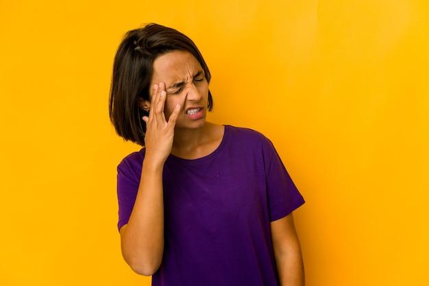 Молодая латиноамериканская женщина изолирована на желтых трогательных висках и имеет головную боль.