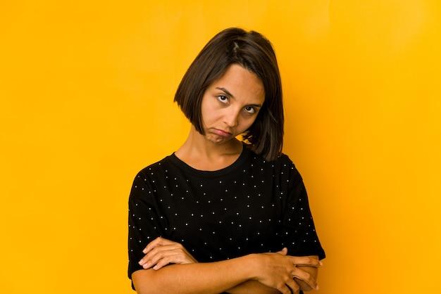 Молодая латиноамериканская женщина изолирована на желтом, которой скучно, устало и ей нужен день отдыха.