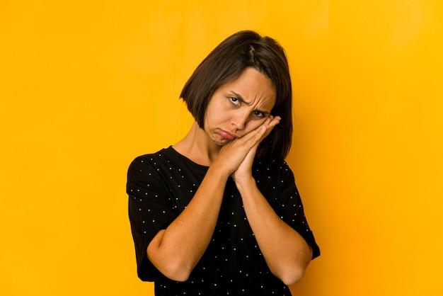 Молодая латиноамериканская женщина, изолированная на желтой зевоте, показывает усталый жест, закрывающий рот рукой.
