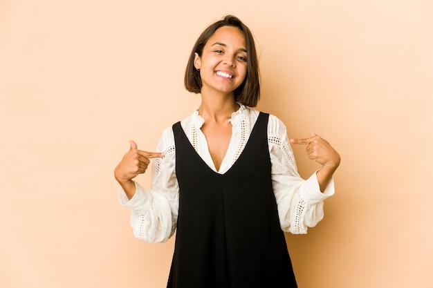 Молодая латиноамериканская женщина изолировала указывает пальцами вниз, положительное чувство.