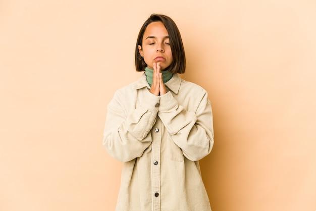 Молодая латиноамериканская женщина изолировала молящуюся, демонстрируя преданность, религиозный человек, ищущий божественного вдохновения. Premium Фотографии