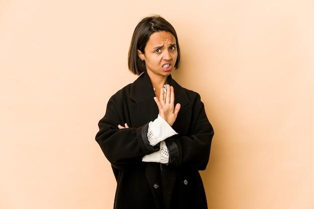 Молодая латиноамериканская женщина изолирована, отвергая кого-то, показывая жест отвращения.