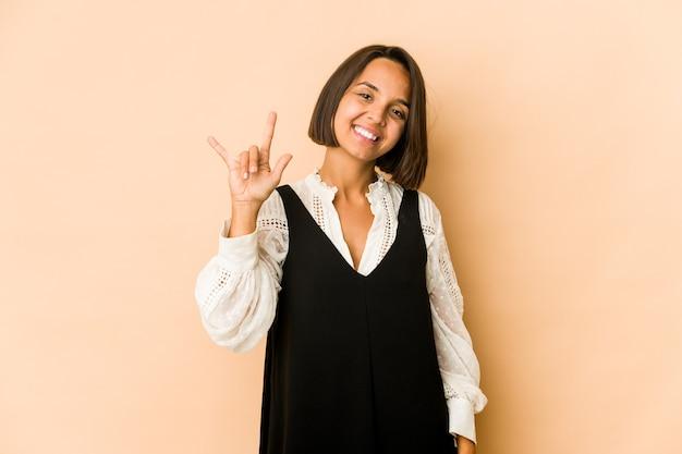 Молодая латиноамериканская женщина изолировала показывая жест рогов как понятие революции.