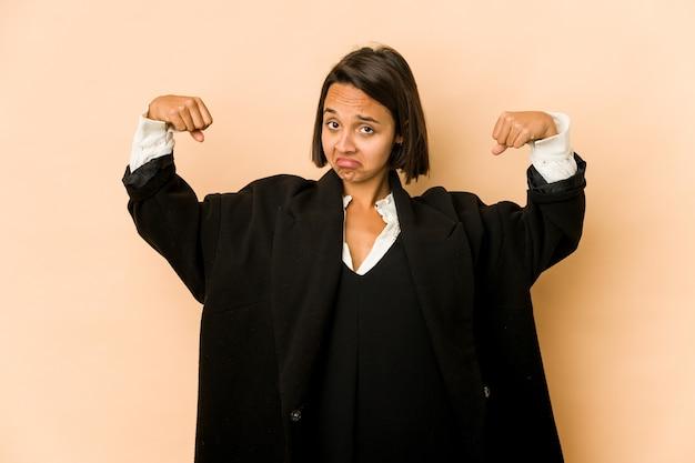 Молодая латиноамериканская женщина изолирована, показывая жест силы руками, символ женской силы