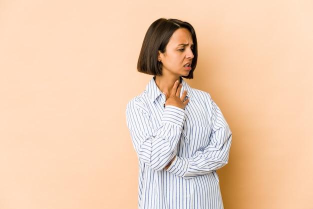 Изолированная молодая латиноамериканка страдает от боли в горле из-за вируса или инфекции.
