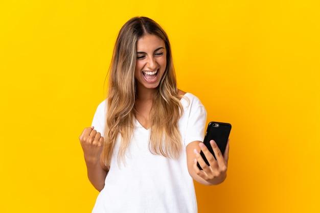 Молодая латиноамериканская женщина изолирована с помощью мобильного телефона и делает жест победы