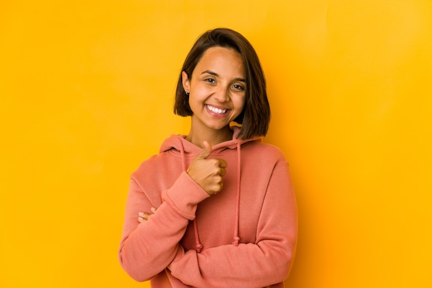 Young hispanic woman isolated on yellow smiling and raising thumb up