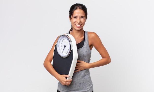 젊은 히스패닉계 여성이 재미있는 농담에 크게 웃으면서 체중계를 들고 있습니다. 다이어트 개념