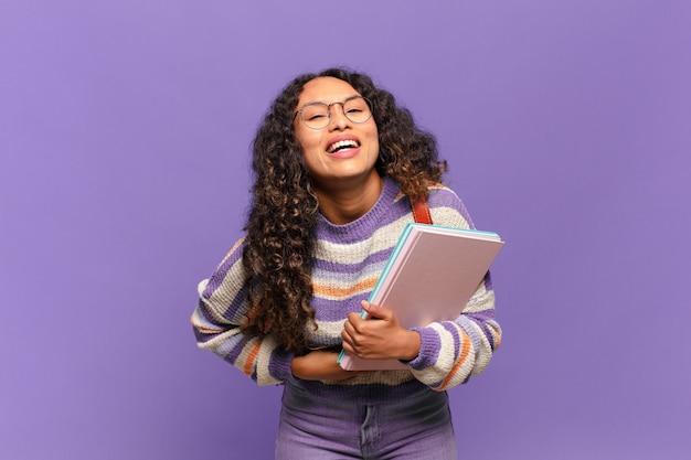 いくつかの陽気な冗談で大声で笑い、幸せで陽気に感じ、楽しんでいる若いヒスパニック系女性。学生の概念