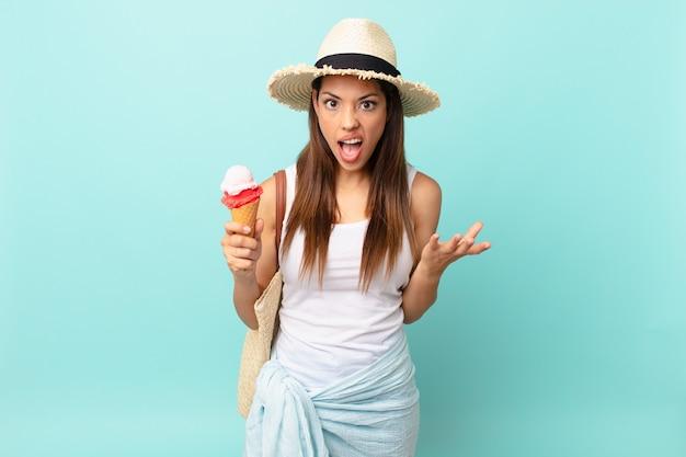 젊은 히스패닉계 여성이 화나고 짜증이 나며 아이스크림을 들고 있습니다. 여름 개념