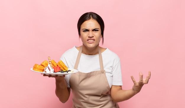 Молодая латиноамериканская женщина выглядит сердитой, раздраженной и разочарованной, кричит, черт возьми, или что с тобой не так