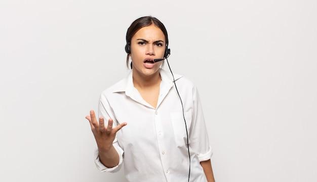 若いヒスパニック女性が怒っているように見え、イライラし、イライラして叫んでいる