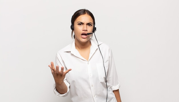 Young hispanic woman looking angry, annoyed and frustrated screaming wtf or whatã¢â€â™s wrong with you