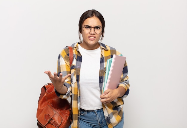 Young hispanic woman looking angry, annoyed and frustrated screaming wtf or what's wrong with you