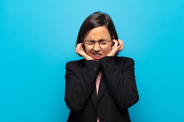 怒っている、ストレスを感じている、イライラしている、耳をつんざくような音、音、または大音量の音楽で両耳を覆っている若いヒスパニック系女性
