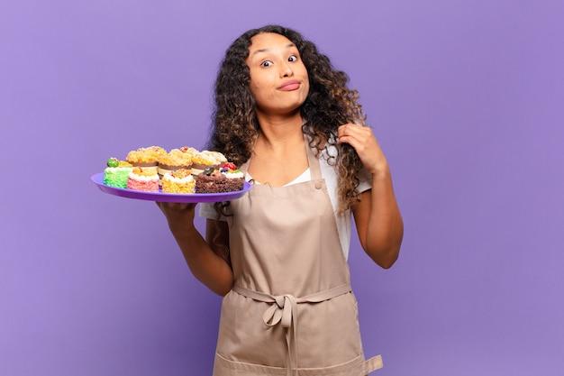 거만하고, 성공하고, 긍정적이고, 자랑스럽고, 자기를 가리키는 젊은 히스패닉 여자. 요리 케이크 개념