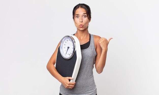 젊은 히스패닉계 여성이 믿을 수 없다는 표정을 짓고 체중계를 들고 있습니다. 다이어트 개념