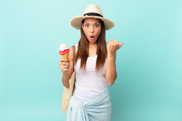 Молодая латиноамериканская женщина, удивленная недоумением и держащая мороженое. концепция шумер
