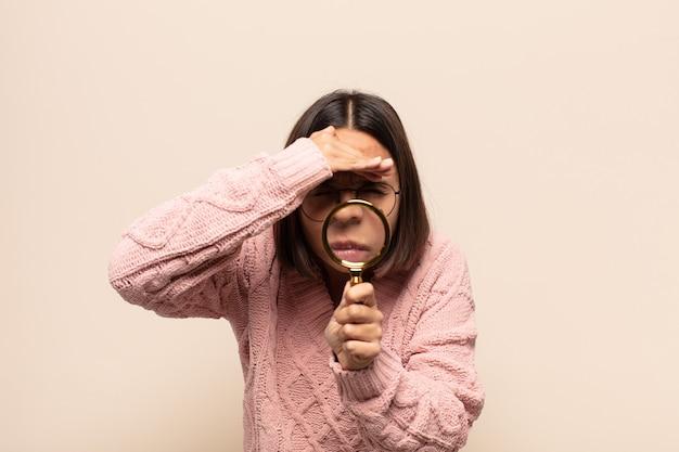 젊은 히스패닉 여자가 어리둥절하고 놀란 표정으로 이마 위로 손을 뻗어 멀리보고, 보거나 검색