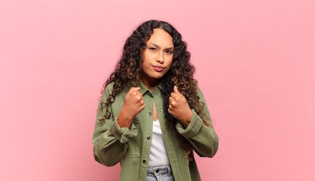 Молодая латиноамериканская женщина выглядит уверенной, сердитой, сильной и агрессивной, с кулаками, готовой к бою в боксерской позе