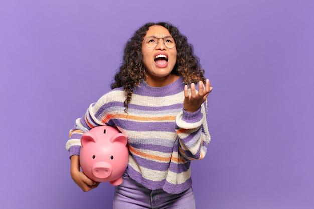 절망하고 좌절하고 스트레스를 받고 불행하고 짜증이 나는 젊은 히스패닉 여성이 소리를 지르고 비명을 지르고 있습니다. 돼지 저금통 개념