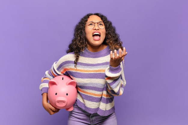 Young hispanic woman looking desperate and frustrated, stressed, unhappy and annoyed, shouting and screaming. piggy bank concept