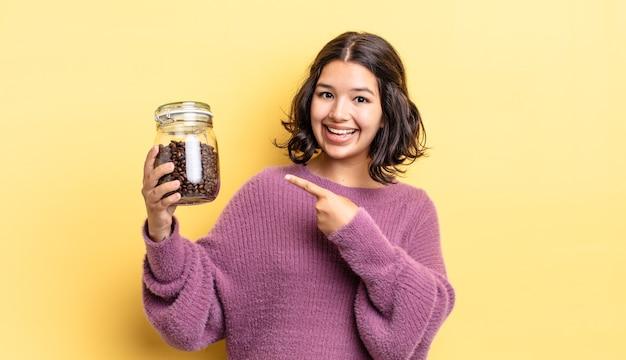 흥분 하 고 놀란 찾고 젊은 히스패닉 여자 측면을 가리키는. 커피 콩 개념