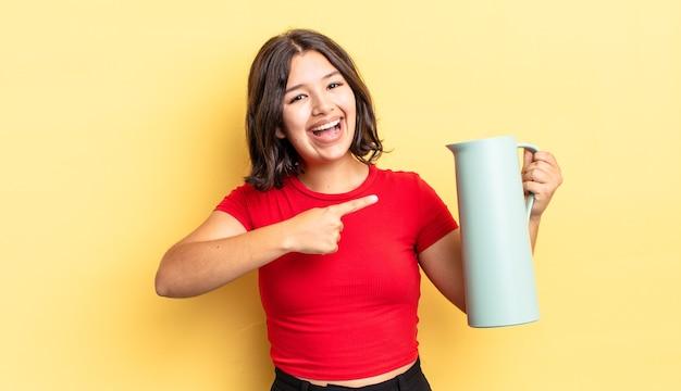 興奮して驚いたように見える若いヒスパニック系女性が横を指しています。魔法瓶のコンセプト