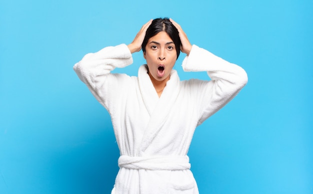Young hispanic woman looking excited and surprised, open-mouthed with both hands on head, feeling like a lucky winner. bathrobe concept