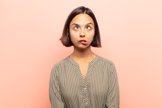 Young hispanic woman looking goofy and funny with a silly cross-eyed expression, joking and fooling around
